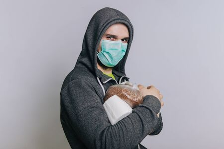 A guy in a gray sweatshirt on a light background in a medical mask holds essential products.