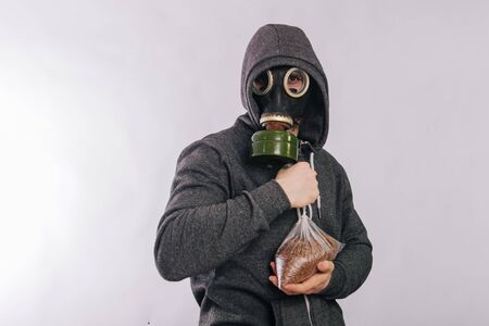 A guy in a gas mask and a gray hoodie is holding a packet of buckwheat. The stink in the toilet. Coronavirus pandemic