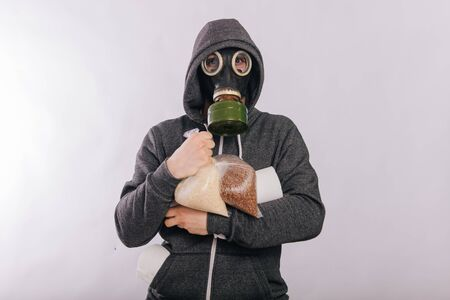 A guy in a gas mask and a gray sweatshirt holds a pack of buckwheat and paper. The stink in the toilet. Coronavirus pandemic