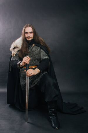 Warrior in armor with a sword. A guy with long hair and a beard, a fox collar. Dressed in chain mail, a black cloak and black pants holds a sword in his hands while sitting on one knee.