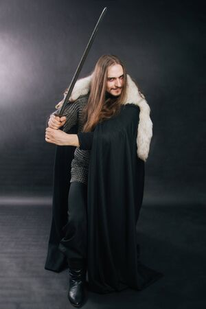 Warrior in armor with a sword. A guy with long hair and a beard, a fox collar. Dressed in chain mail, a black cloak and black pants holds a sword in his hands. Studio photo against a dark background. Stok Fotoğraf