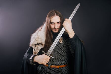 Knight in chain mail and with a fur collar on a black cloak on a gray background. Portrait of a Viking man with long hair and a beard in armor holds a sword. Banque d'images