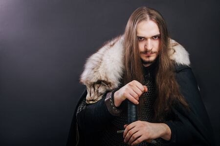 Knight in chain mail and with a fur collar on a black cloak on a gray background. Portrait of a Viking man with long hair and a beard in armor holds a sword. Stock Photo