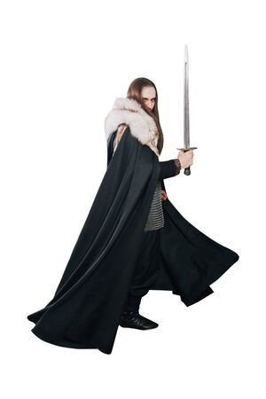 A knight in chain mail and with a fur collar in a black cloak on a white background in full growth. Viking man with long hair and a beard in armor holds a sword.