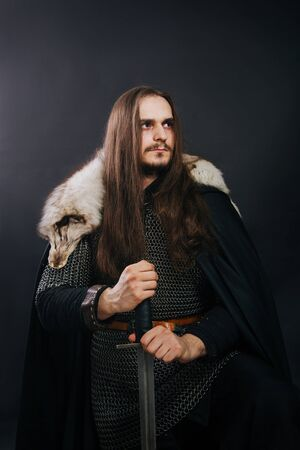 Knight in chain mail and with a fur collar on a black cloak on a gray background. Portrait of a Viking man with long hair and a beard in armor holds a sword. Stockfoto