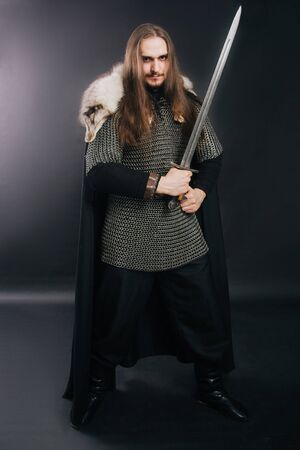 Warrior in armor with a sword. A guy with long hair and a beard, a fox collar. Dressed in chain mail, a black cloak and black pants holds a sword in his hands.