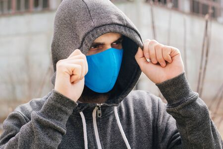 A guy in a gray sweater with a blue medical mask. Holds a hood with his own hands. Against the background of destroyed and abandoned buildings. Quarantined man.