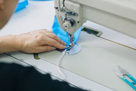 Stepwise stitching of blue fabric medical masks on a sewing machine. A close up of an industrial sewing machine makes a seam. Banque d'images