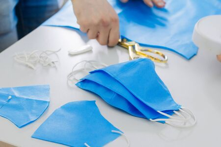 Creating handmade medical masks. Sewing protective masks at home. Cut on the table. The work of a seamstress in quarantine.