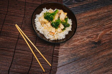 Green cabbage broccoli with rice and white meat. On a dark Chinese chopsticks