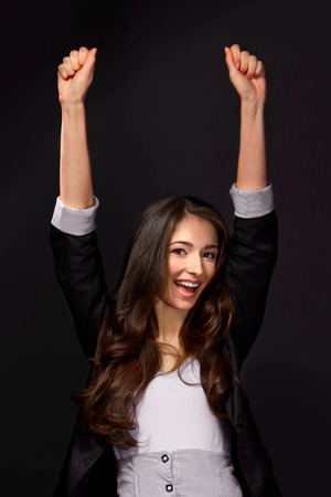 businesswoman suit: Studio shot of an attractive young woman with her arms raised in celebration Stock Photo