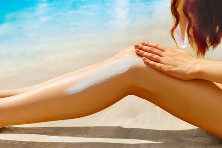 Woman apply sun protection cream on her smooth tanned legs