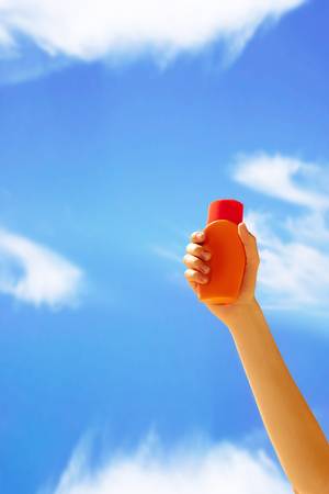 suncare: Close up of a female hand holding sun cream bottle.