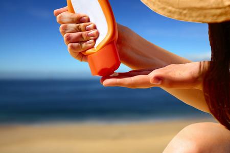 Primo piano a mano spremere crema blocco sole da un tubo