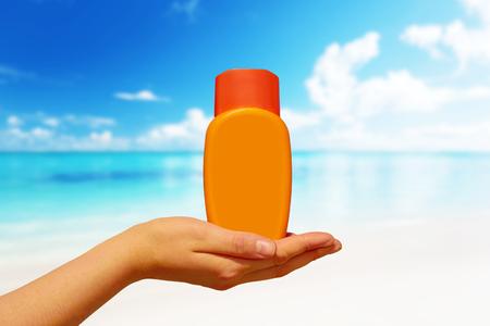 suncream: Female hand with suncream bottle background blue heaven Stock Photo