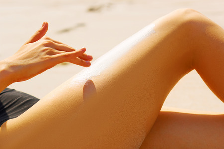 Portrait of woman applying sunscreen on her sexy legs at beach