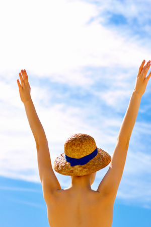 Young woman on the beach with raised arms enjoying the sun