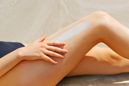 sun screen: Closeup on female hand applying sun screen creme on leg Stock Photo