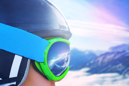 Reflection of the winter mountain landscape in a ski mask.