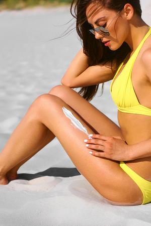 Woman applying sunblock cream on leg at the beach.