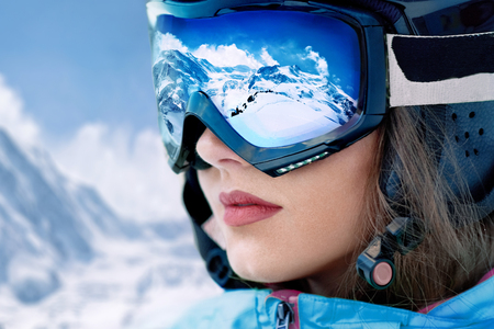 Portrait of young woman at the ski resort on the background of mountains and blue sky.A mountain range reflected in the ski mask Stock fotó