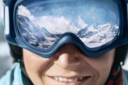 Nahaufnahme der Skibrille eines Mannes mit der Reflexion verschneiter Berge. Eine Bergkette spiegelt sich in der Skimaske wider. Mann auf dem blauen Himmel des Hintergrundes. Skibrille tragen. Wintersport.