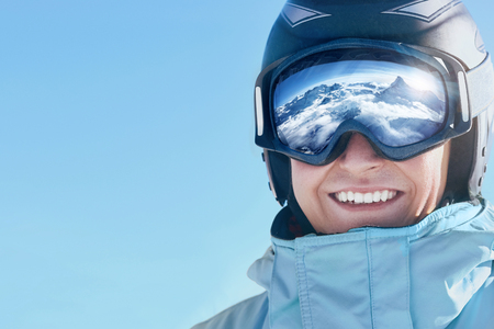 Close up of the ski goggles of a man with the reflection of snowed mountains.  A mountain range reflected in the ski mask.  Portrait of man at the ski resort.  Wearing ski glasses. Winter Sports.