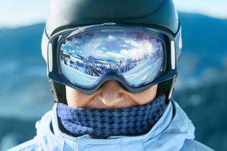 Close up of the ski goggles of a man with the reflection of snowed mountains. A mountain range reflected in the ski mask. Portrait of man at the ski resort on the background of mountains and sky