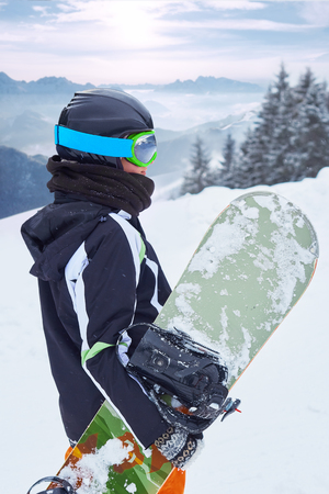 Female snowboarder  standing with snowboard in one hand and enjoying alpine mountain landscape - snowboarding concept 版權商用圖片