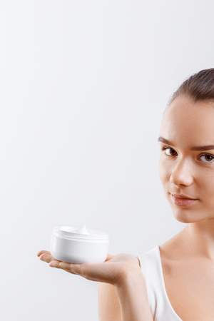 Beauty Concept. woman holds a cream in her hand and spreads it on her face to moisturize her skin and wrinkle from impurities. body care, skincare.Taking good care of her skin