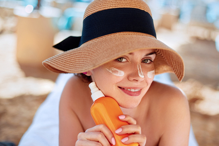 Facial Care. Young  Female Holding Bottle Sun Cream and  Applying on Face Smiling. Beauty Face.  Portrait Of Young Woman in hat Smear  Moisturizing Lotion on Skin. SkinCare
