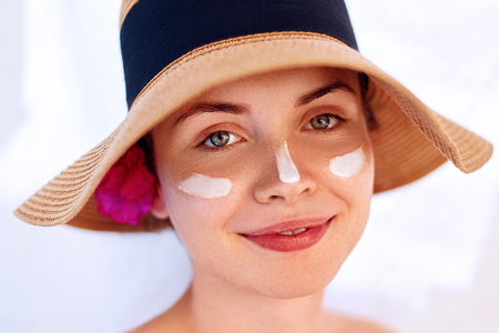 Woman smile applying sun cream  on face. Skincare. Body Sun protection. sunscreen. Female in hat smear  moisturizing lotion on skin. 版權商用圖片