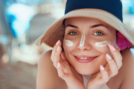 Skincare. Beauty Concept. Young pretty woman applying sun cream and touch own face. Female in hat smear sunscreen lotion on skin. Skin Protection and dermatology.