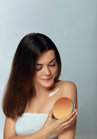 Beauty Concept. Woman Holds a Cosmetic Crem in her Hand and Spreads it on Her Shoulder  to Moisturize her Skin. Female Applying Cream and Smiling. Beauty Face.  Body Care, Skincare.