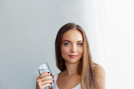Mode de vie sain. Jeune femme buvant dans un verre d'eau douce. Soins de santé. Boissons. Portrait d'un modèle féminin souriant heureux tenant un verre transparent. Concept de santé, beauté, régime. Alimentation équilibrée.