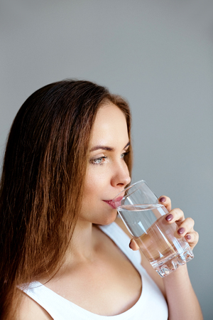 Healthy lifestyle. Young woman show glass of water. Girl drinks water. Portrait of happy smiling female model holding transparent glass of water. Health,Beauty, Diet concept