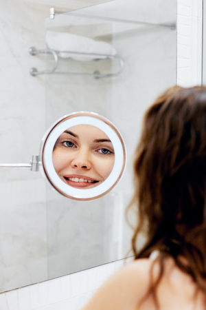 Skin care. Woman touching hair and smiling while looking in the mirror.Portrait of happy girl with wet hair in bathroom Фото со стока