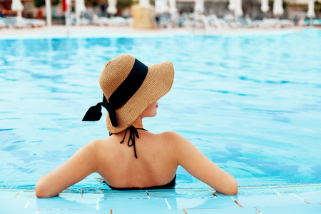 Beautiful Sexy Girl With Healthy Skin In Bikini, Sun Hat Relaxing In Swimming Pool Water In Resort Spa Hotel On Travel Holidays Vacation.