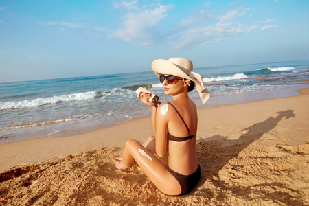 Beautiful Woman in Bikini Applying Sun Cream on Tanned  Shoulder. Sun Protection. Skin and Body Care. Girl Using Sunscreen to Skin. Portrait Of Female Holding Suntan Lotion and Moisturizing Sunblock. Banque d'images