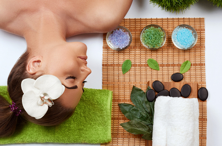 Face massage. people, beauty, spa, healthy lifestyle and relaxation concept - close up of beautiful young woman lying with closed eyes and having face or head massage in spa