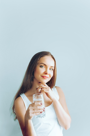 Healthy lifestyle. Young woman show glass of water. Girl drinks water. Portrait of happy smiling female model  holding transparent glass of water. Health,Beauty, Diet concept Banque d'images