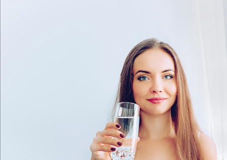 Healthy Diet Nutrition. Portrait Of Beautiful Young Woman Taking Vitamin Pill looking in windows. Closeup Of Happy Girl Holding Colorful Capsule Pill And Glass Of Fresh Water.