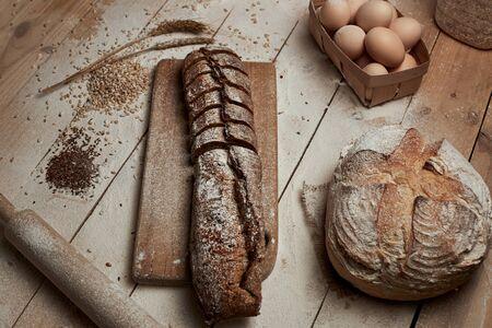 Freshly baked bread .Top view of sliced wholegrain bread on dark rustic wooden  background closeup. Bread at leaven. Unleavened bread.