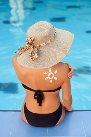 Sunscreen. Sunblock. Woman putting solar cream on shoulder  outdoors by pool under sunshine on beautiful summer day. Skin care.