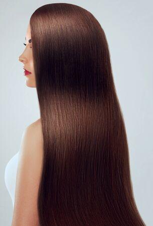Bei capelli. Donna di bellezza con capelli lunghi lussuosi. Ragazza di modello di bellezza con capelli castani sani. Bella femmina con lunghi capelli lisci lucidi e lisci. Acconciatura. Raddrizzamento alla cheratina.