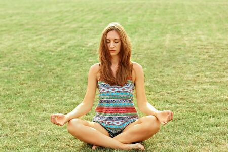 Beauty woman practices yoga and meditates in the lotus position in the park. Meditation.  Active Lifestyle. Healthy and yoga concept. Fitness and sports Stock fotó