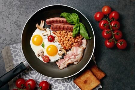 English breakfast in cooking pan with fried eggs, sausages,beans, tomatoes, mushrooms, bacon and toast on wooden background.  Copy space. Top view