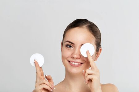 Beauty portrait of a cheerful young woman removing face make-up with a cotton pad