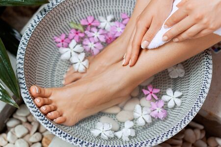 Perfect clean female feet . Beautiful and elegant groomed girls hand touching  her foot . Spa ,scrub and foot care. Massage Stock Photo