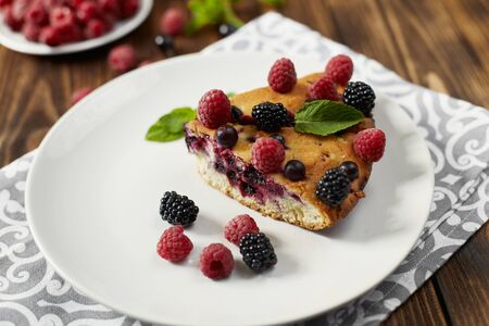 Piece of pie with blueberries on a plate, napkin on a wooden boards background Reklamní fotografie